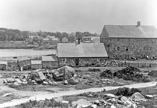 The Candle House, at right in the photo from about 1890, is all that remains of mid-nineteenth-century whaling in Woods Hole. The smaller building at center housed the try works, where whale oil was rendered. Today the Candle House is used by the Marine Biological Laboratory (MBL) for offices. (Photo by Baldwin Coolidge, Marine Biological Laboratory Archives)