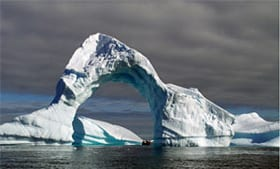 Erosion has carved an icy arch into this Antarctic iceberg found near Booth Island, Lemaire Channel. (Photo by Pat Lohmann, Woods Hole Oceanographic Institution)