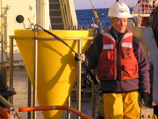 Sediment traps are some of the biggest instruments used in ocean moorings. The funnel openings are made large to catch enough sediment for analyses. Here, Cynthia Pilskaln, of Bigelow Laboratory for Ocean Sciences, heads out on R/V Oceanus to deploy a trap. (Patrick Rowe, WHOI)