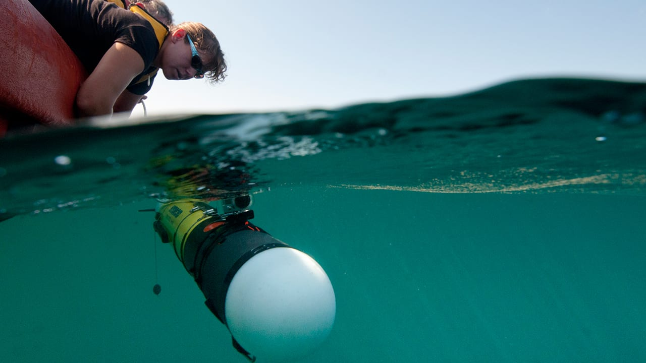 Engineer Amy Kukulya launches a REMUS 100 autonomous underwater vehicle (AUV). (Photo by Chris Linder, Woods Hole Oceanographic Institution)