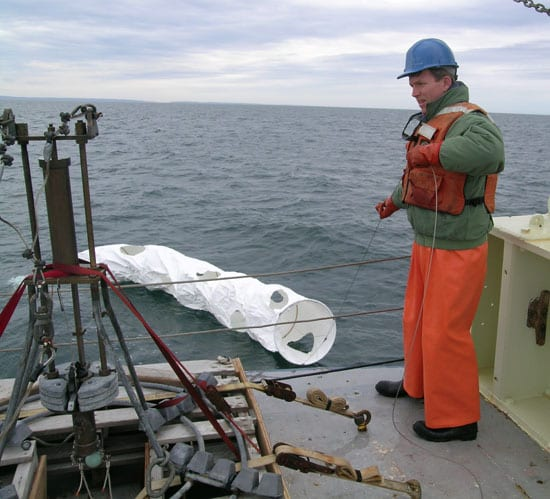 Dennis McGillicuddy launches a satellite-tracked drifter into the Bay of Fundy to examine how ocean currents circulate water and the harmful algae Alexandrium into and out of the bay. McGillicuddy led the first COHH-sponsored research expedition in May 2005 on R/V Oceanus. (Photo by Mike Carlowicz, Woods Hole Oceanographic Institution)