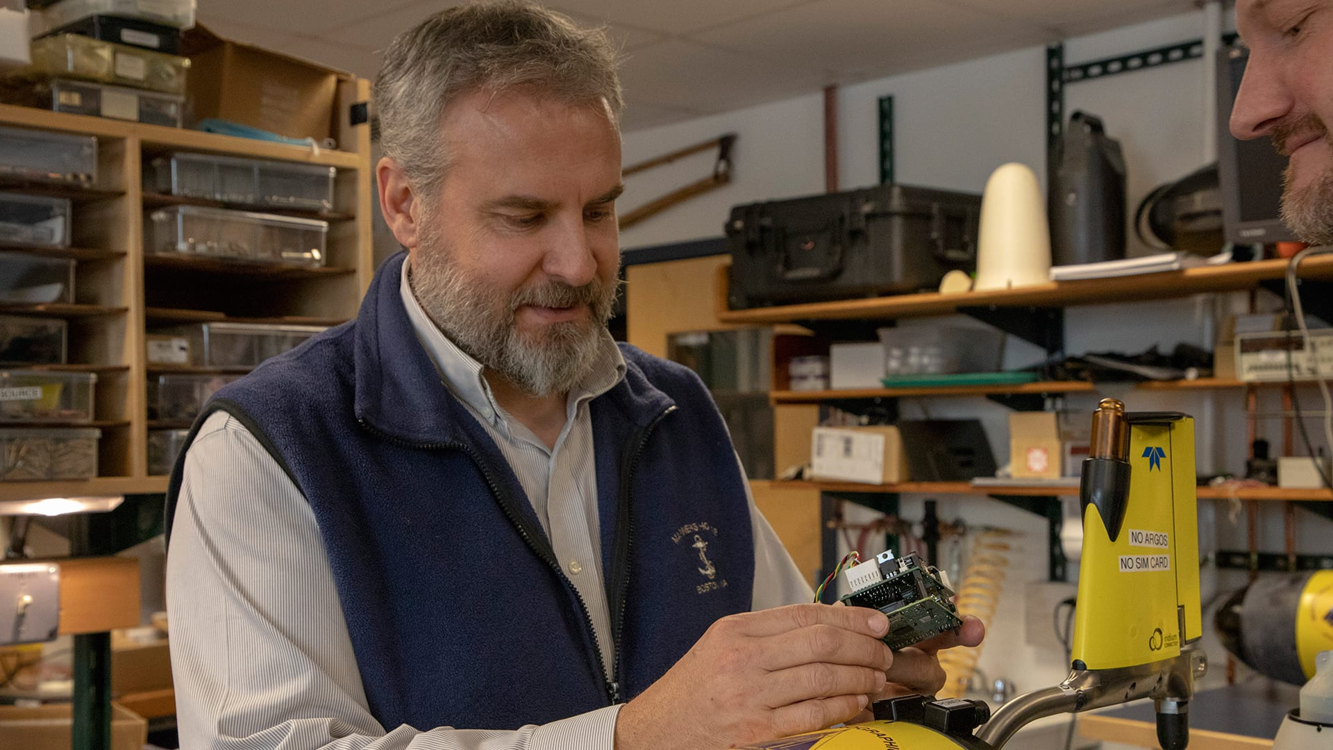 "WHOI scientist Rich Camilli holds the ""brains"" of the under-ice glider—a low-power microcomputer which provides enough processing power to interpret the glider's sensor data onboard and run adaptive mission plans that help it safely navigate its environment."