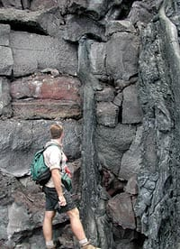 Greg Kurras, a student at U. Hawaii, SOEST, standing at the beach cliff at the shoreline where the Pu'u Oo eruption was entering the sea in June, 2001. Note the layers of lava, each about 1 meter thick. Note also the narrow flow that has cascaded down from a small tube in one of the flows at the top of the photograph. The next photo shows a close up of this small lava tube. Scale from top to bottom of image is about 5 meters.