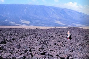 A'a lava field on Fernandina, Galápagos, on the northwest coastline. Walking across a flow like this can be an extremely painful experience. Note the 'tortoise-shell' profile of the volcano's summit in the background