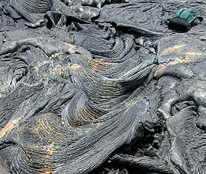 Pahoehoe lava transitioning into ropy pahoehoe (at left of photograph) on Kilauea volcano, Hawaii. Daypack at upper right for scale.