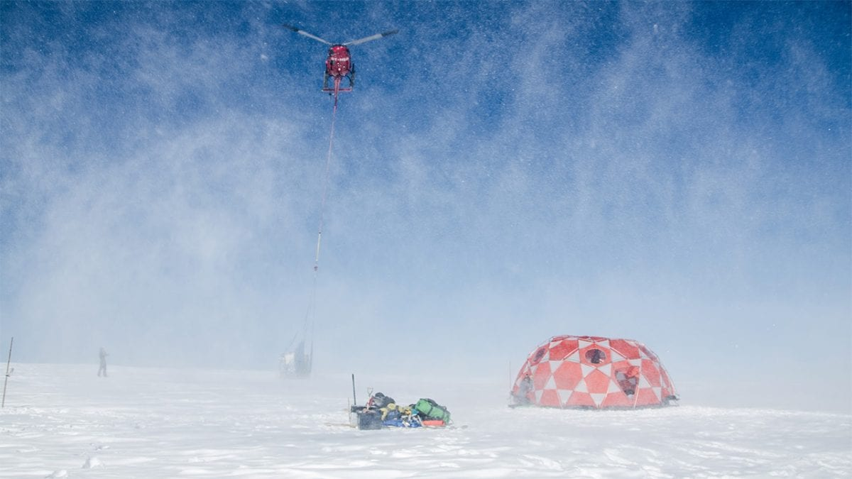 A helicopter takes off with a sling-load of freshly-drilled ice cores taken from the 2000-meter-high summit of an ice cap in west Greenland.