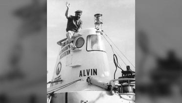 HOV <em>Alvin</em> pilot Valentine Wilson sits atop the research submarine in 1966, shown here in its first incarnation. After Wilson came back from a trip to the Bahamas sporting a red beret, the hats were adopted as a badge of camaraderie among the members of the #HOVAlvin group. Photo by Woods Hole Oceanographic Institution.