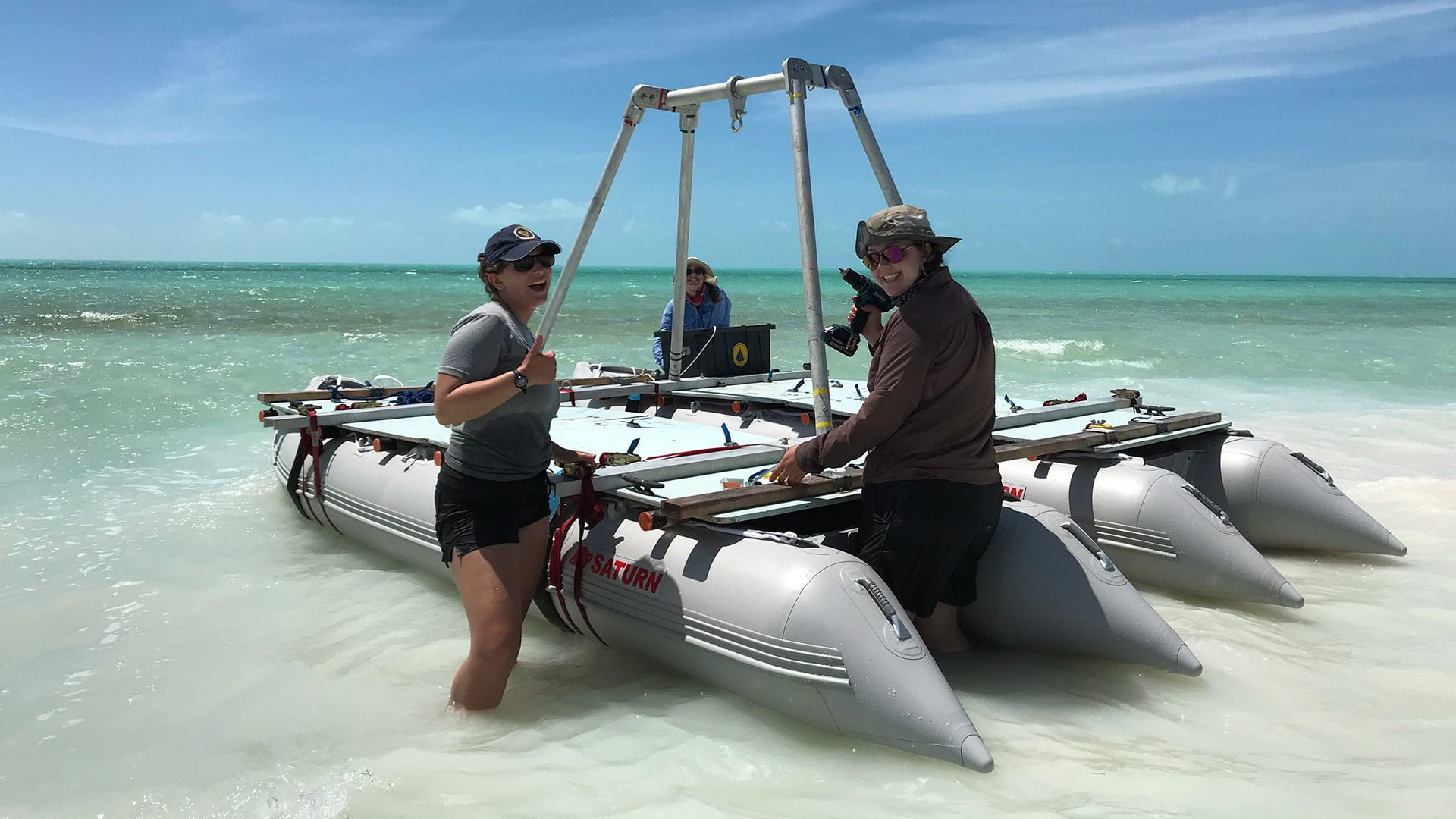 WHOI researchers Lizzy Soranna (front left), Lizzie Wallace (front right), and Nicole D'Entremont head out to conduct hurricane research in an azure-colored marine sinkhole—formally known as a blue hole—off Caicos Island in the Caribbean. They collected sediment samples from the bottom of the hole to learn more about the characteristics of Hurricane Irma, a Category 5 storm that passed over the area in early September of 2017. (Photo by Rose Palermo, Woods Hole Oceanographic Institution).