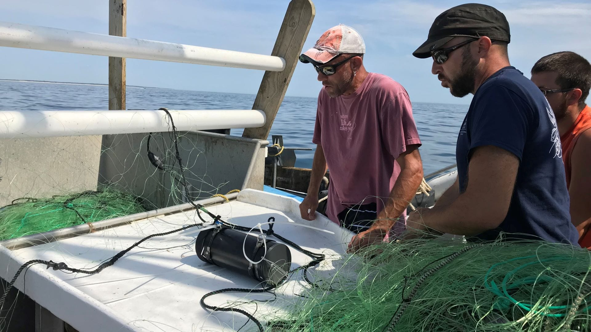 Commercial fisherman Doug Feeney (left) and scientist Owen Nichols from CCS mount one of five underwater cameras on the headrope of a gillnet