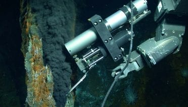 The manipulator arm of the remotely operated vehicle Jason samples a stream of fluid from a hydrothermal vent. The fluid contains gases that are in liquid form because of the high pressure of the deep ocean.