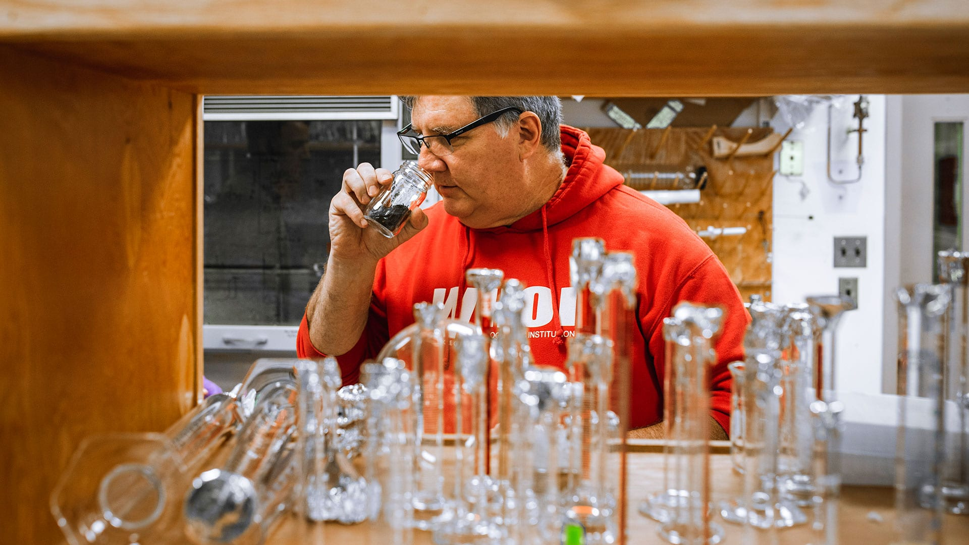 Senior researcher and WHOI marine geochemist, Bob Nelson, notices the diesel-like odor in a small bisection of a sediment core from Wild Harbor – a sign of the oil that remained 50 years after the spill. (Photo by Daniel Hentz, Woods Hole Oceanographic Institution)