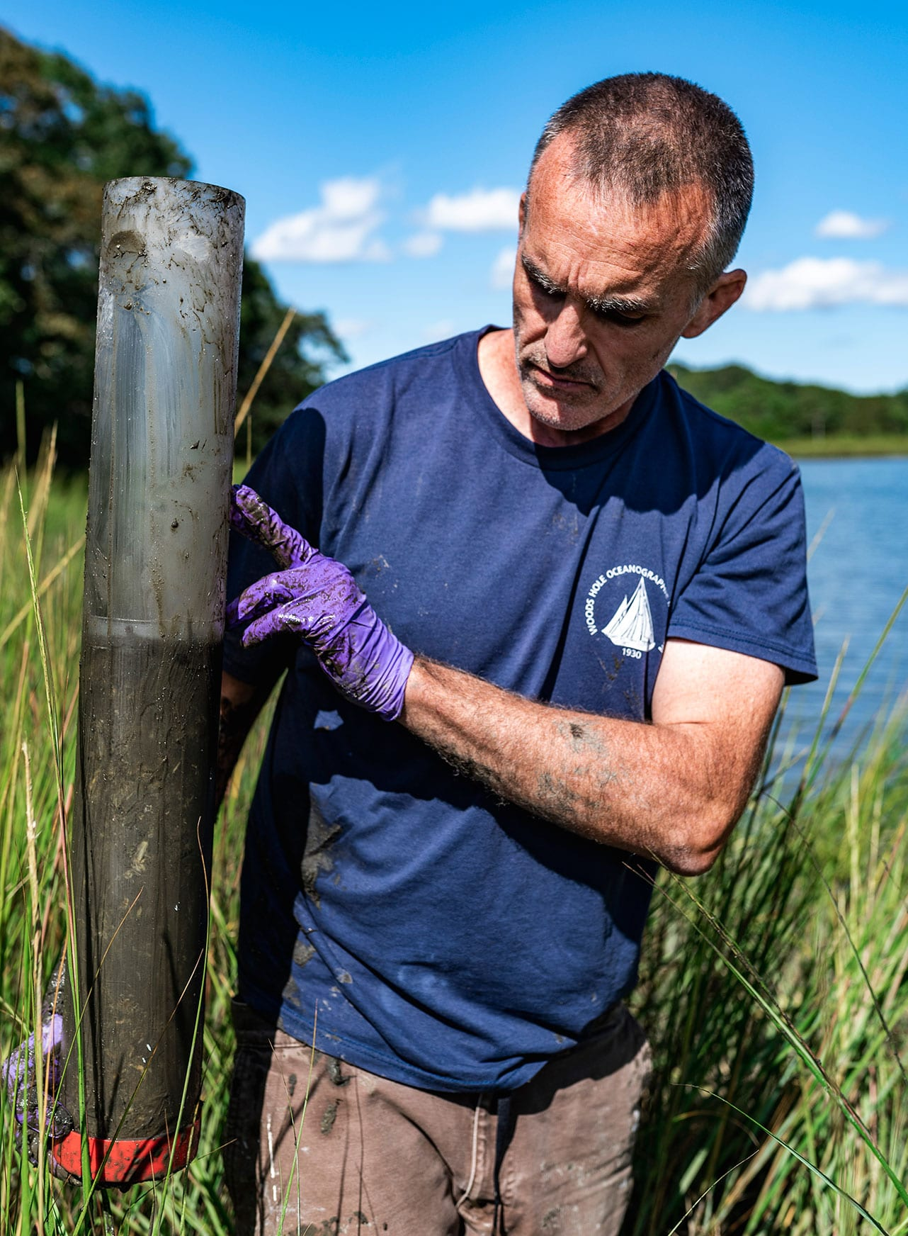 WHOI marine geochemist, Christopher Reddy, holds up a PVC pipe core of the sediment, something he calls a natural tape recorder for what happened to the land throughout the years. This includes the West Falmouth Oil Spill, which can be detected six inches deep in soil. (Photo by Daniel Hentz, Woods Hole Oceanographic Institution)