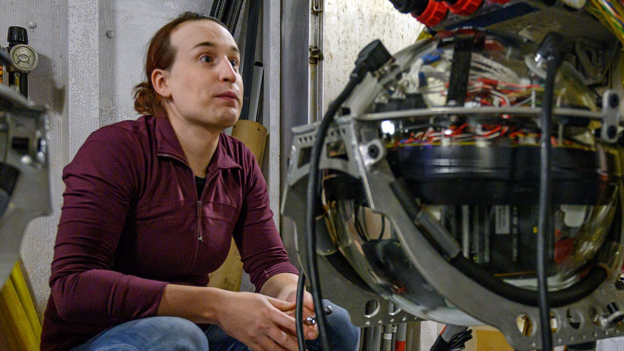 WHOI mechanical engineer Casey Machado sits in the ship's staging bay before Orpheus' first plunge of the expedition. The vehicle's electronics are housed in a glass sphere, shown in the foreground, which can tolerate the extreme pressure of the deep, and is one of many cost-saving measures that went into the vehicle's design. (Photo by Evan Lubofsky, Woods Hole Oceanographic Institution)