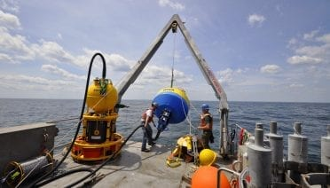 Jeff Pietro and Will Ostrom deploying an Environmental Sample Processor surface buoy. Photo by Ashley Cryan, Woods Hole Oceanographic Institution