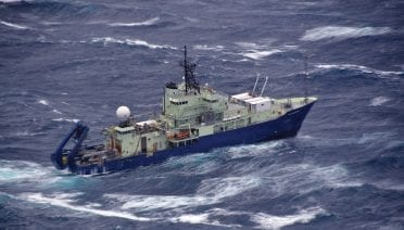 The R/V <em>Atlantis</em> rides out stormy seas in the North Atlantic during NASA's Aerosols and Marine Ecosystems Study (NAAMES) cruise to study the processes associated with the world's largest phytoplankton bloom. This image was shot from the NASA C-130 aircraft during a storm at the end of the expedition. (Photo by John Hair, NASA)