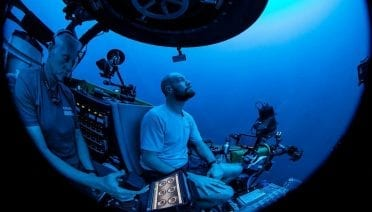 Paul Caiger descends to the ocean twilight zone on the OceanX submersible, <em>Nadir</em>, with pilot Alan Scott at the controls. (Photo by © OceanX Media)