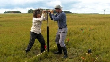 Margot Saher (left) of Bangor University and Roland Gehrels of University of York work together to obtain a sediment core from Barn Island salt marsh in Stonington, Conn. (Image Courtesy of Roland Gehrels, University of York)