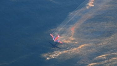 An aircraft releases chemical dispersant on 5 May 2010 over oil floating on the surface of the Gulf of Mexico that was spilled during the Deepwater Horizon disaster. (Photo by U.S. Coast Guard Petty Officer 3rd Class Stephen Lehmann)