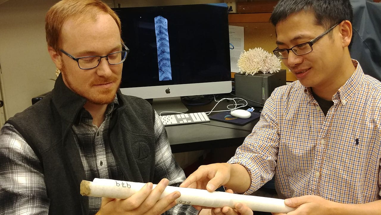 MIT-WHOI Joint Program student Nathaniel Mollica (left) and WHOI scientist Weifu Guo examine a core extracted from a coral skeleton. Photo by Anne Cohen Lab, ©Woods Hole Oceanographic Institution