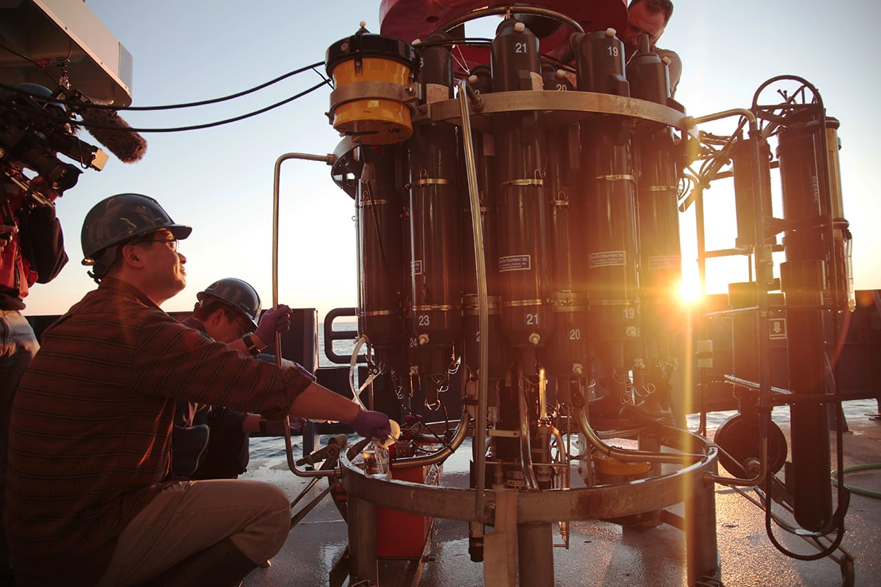 WHOI marine chemist Aleck Wang recovers samples from a CTD during a 2016 research cruise aboard the R/V <em>Neil Armstrong</em>, deployed along the New England Continental Shelf in the vicinity of the Ocean Observatories Initiative Pioneer Array. (Photo by Elise Hugus, UnderCurrent Productions)