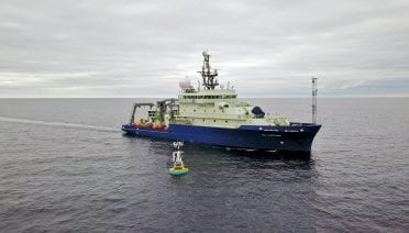 The OOI surface buoy (shown here in 2018 being serviced by the WHOI-operated research vessel Neil Armstrong) will help provide crucial verification of USV and satellite-based models of air-sea interaction in difficult-to-reach high-latitude waters of the North Atlantic and Arctic Oceans. Photo by James Kuo, ©Woods Hole Oceanographic Institution