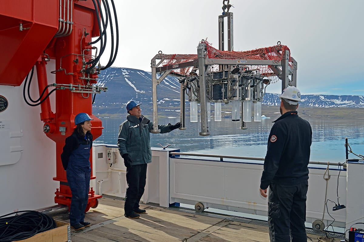 WHOI scientist Don Anderson (center) gently guides an instrument known as a multi-corer as it's lowered to the ocean bottom off the west coast of Greenland. The instrument takes eight individual sediment core samples from the bottom, which scientists use to look for the presence of seed-like cysts released by harmful algae. (Photo by Nicole D'Entremont, © Woods Hole Oceanographic Institution)
