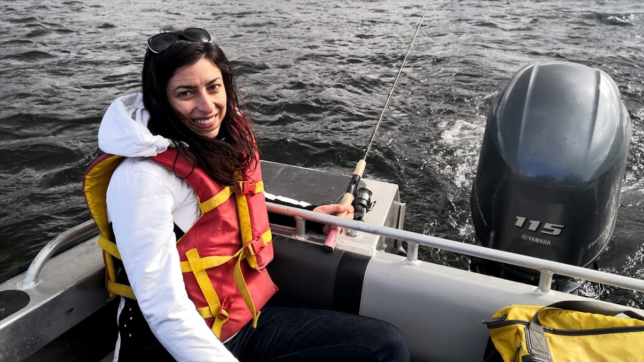 Melina Kourantidou, a post doctorate fellow and fisheries economist at WHOI's Marine Policy Center, fishes for Arctic Char, one of the most prevalent and traditionally consumed fish species in the Nunatsiavut region. (Photo by Rachel Cadman, Dalhousie University)