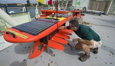 Former WHOI physical oceanographer Dave Fratantoni inspects a Wave Glider on the deck of R/V Knorr in 2012. The Wave Glider uses wave motion to propel itself through the ocean and solar-charged batteries to power its data collection sensors. (Tom Kleindinst, Woods Hole Oceanographic Institution)