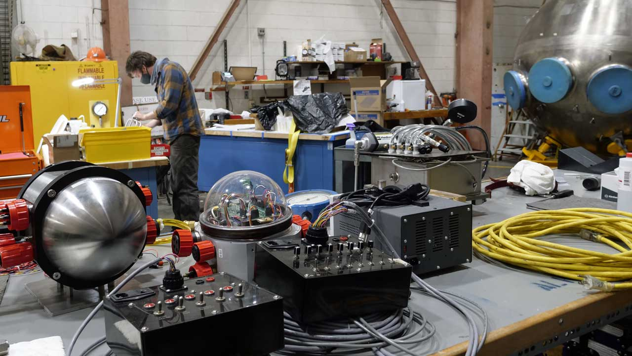 Danik Forsman in the WHOI High Bay working on the new variable ballast pump for Alvin. Sub sphere, right.
