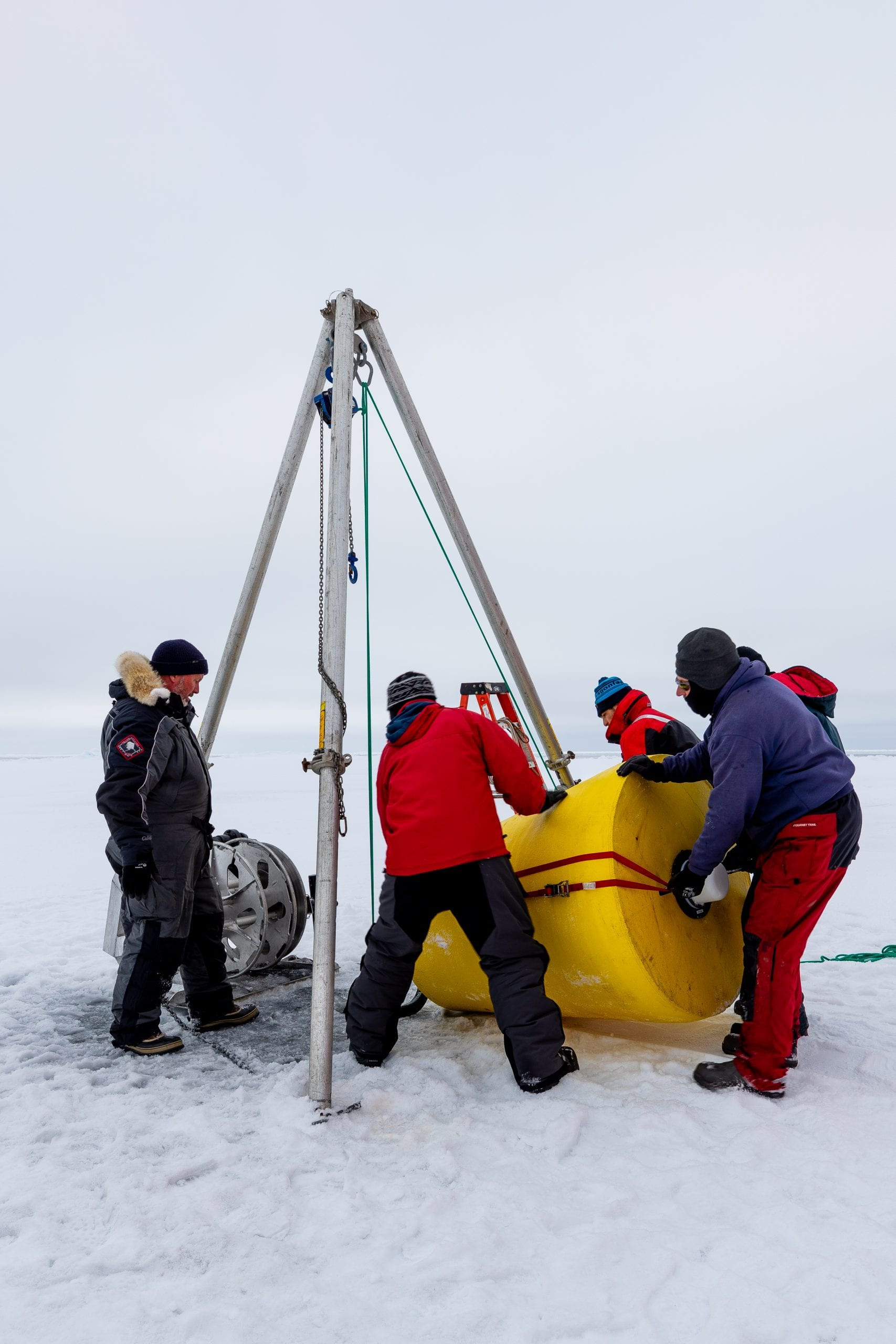 Four people position a yellow mooring under a metal gantry positioned over a hole in the sea ice.