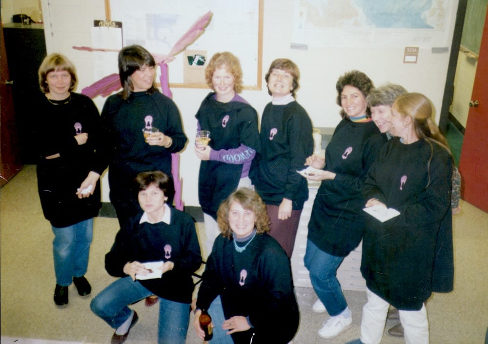 Nine women wearing Data Dolly shirts pose for a photo in the late 70s.