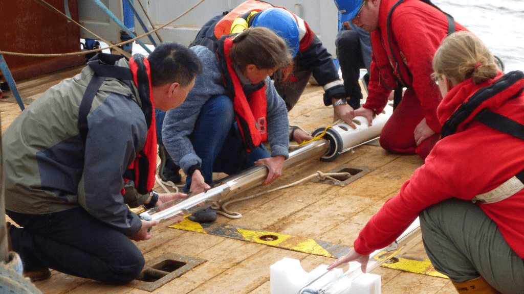 Science and ship's crew on deck preparing a subsurface float for deployment at sea.