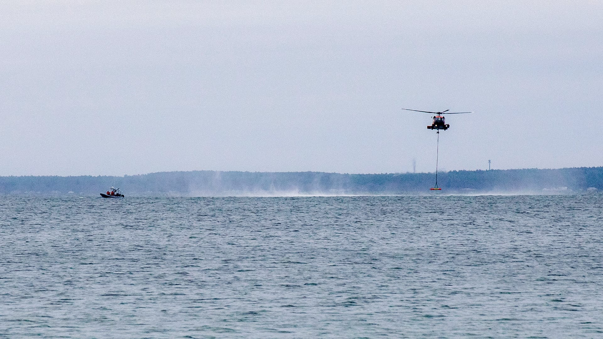 A USCG Jayhawk helicopter releases LRAUV near the Scibotics Team aboard a Zodiac in Buzzards Bay, where the team can inspect the vehicle's systems underwater. (Jayne Doucette, © Woods Hole Oceanographic Institution)