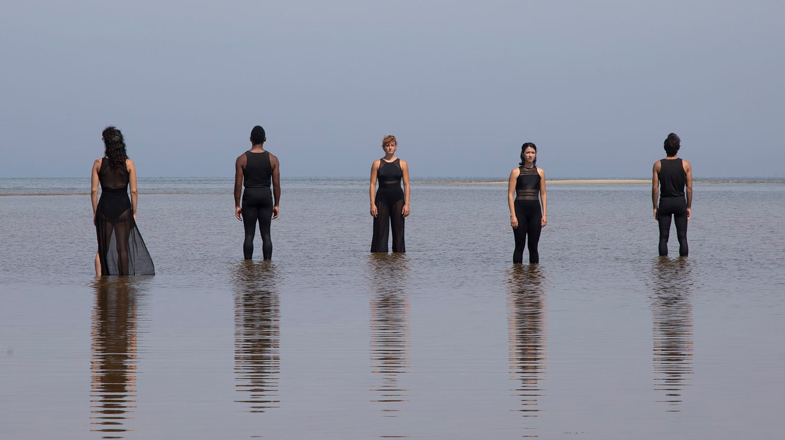 Performers from the Boston Dance Theater pose amid the rising tide along the Cape Cod coastline. (Photo courtesy of Larry Pratt, © Boston Dance Theater)