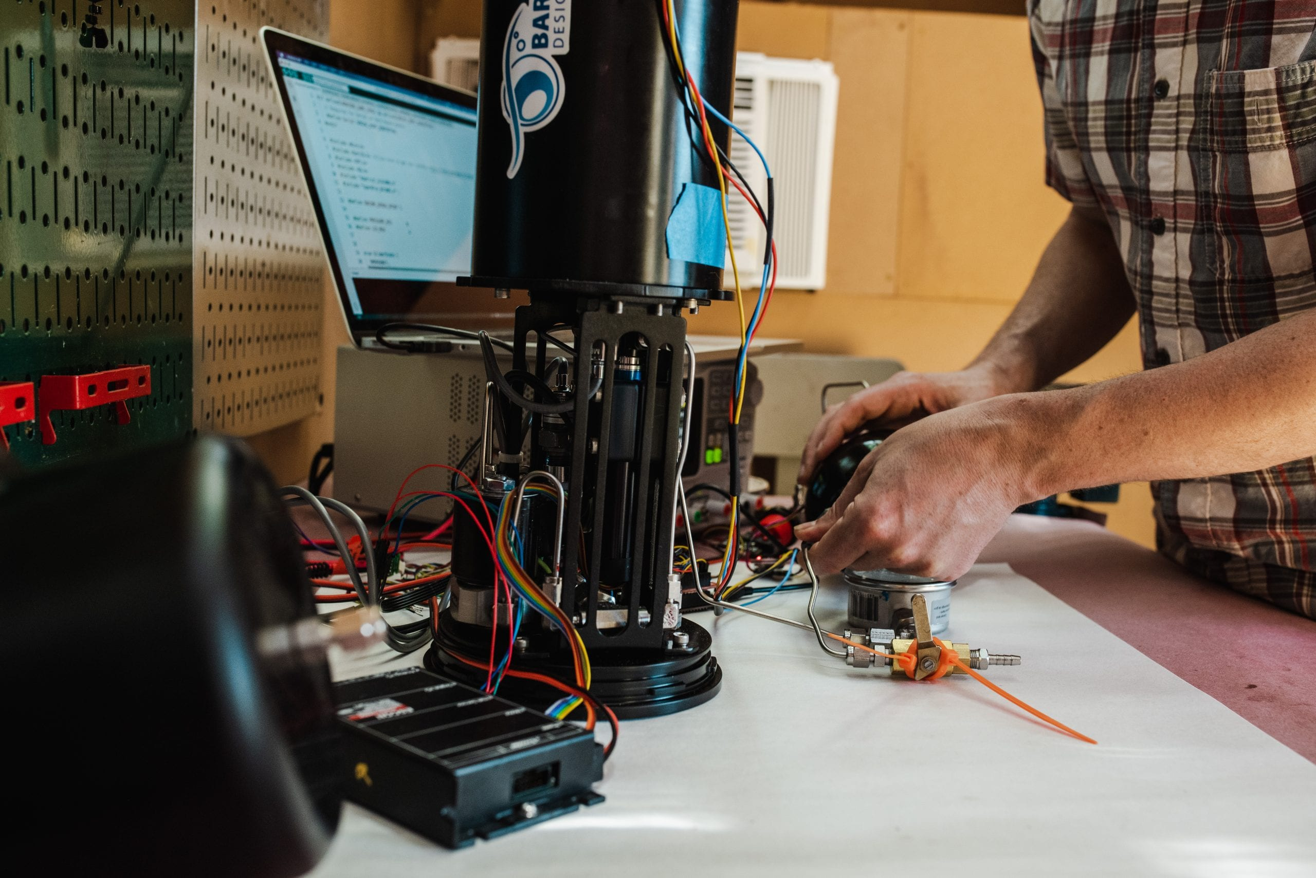 John Reine tests the responsiveness of an open-source buoyancy engine, designed by a former WHOI-engineer Jeremy Paulus, in his shed. (Daniel Hentz, © Woods Hole Oceanographic Institution)