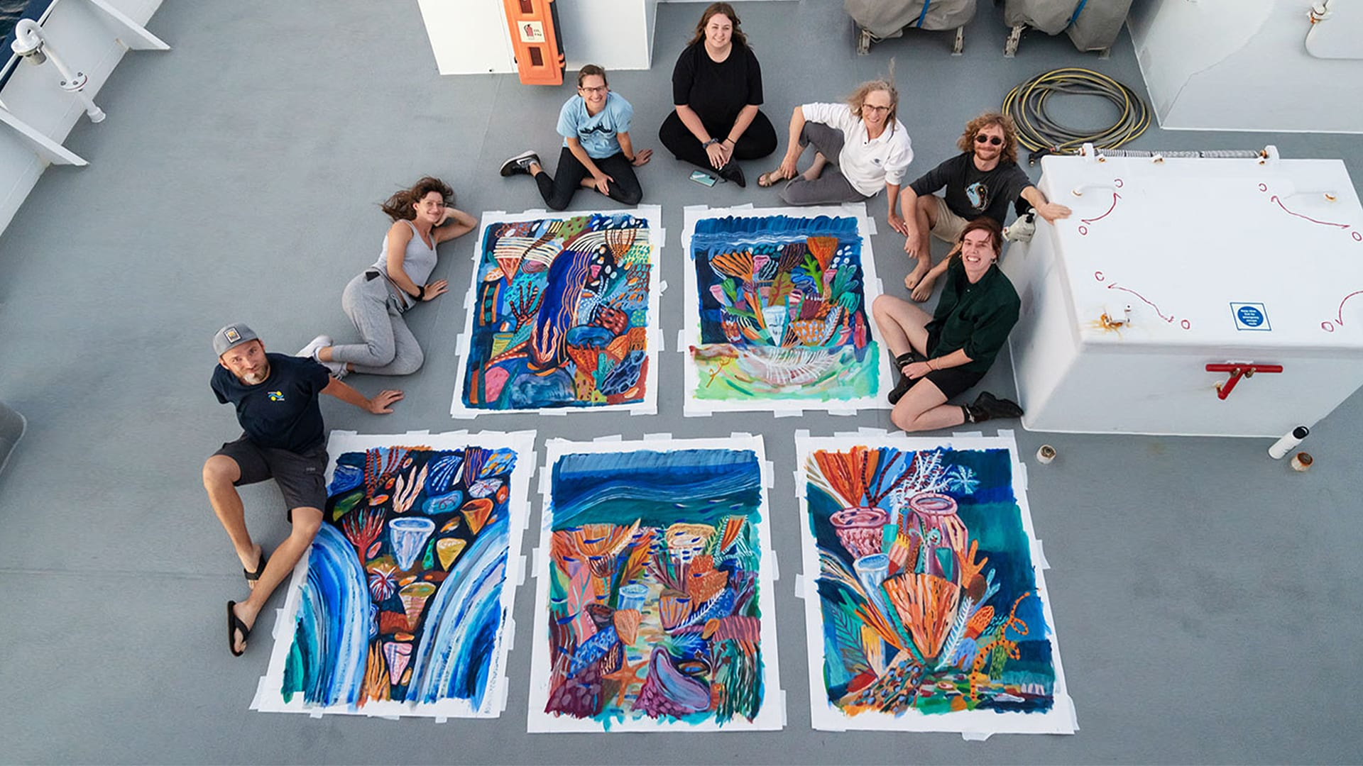 Five art works created by Artist-at-Sea Ellie Hannon (far right) are photographed on the bow of R/V Falkor with members of the science team. (Photo courtesy of © Schmidt Ocean Institute)