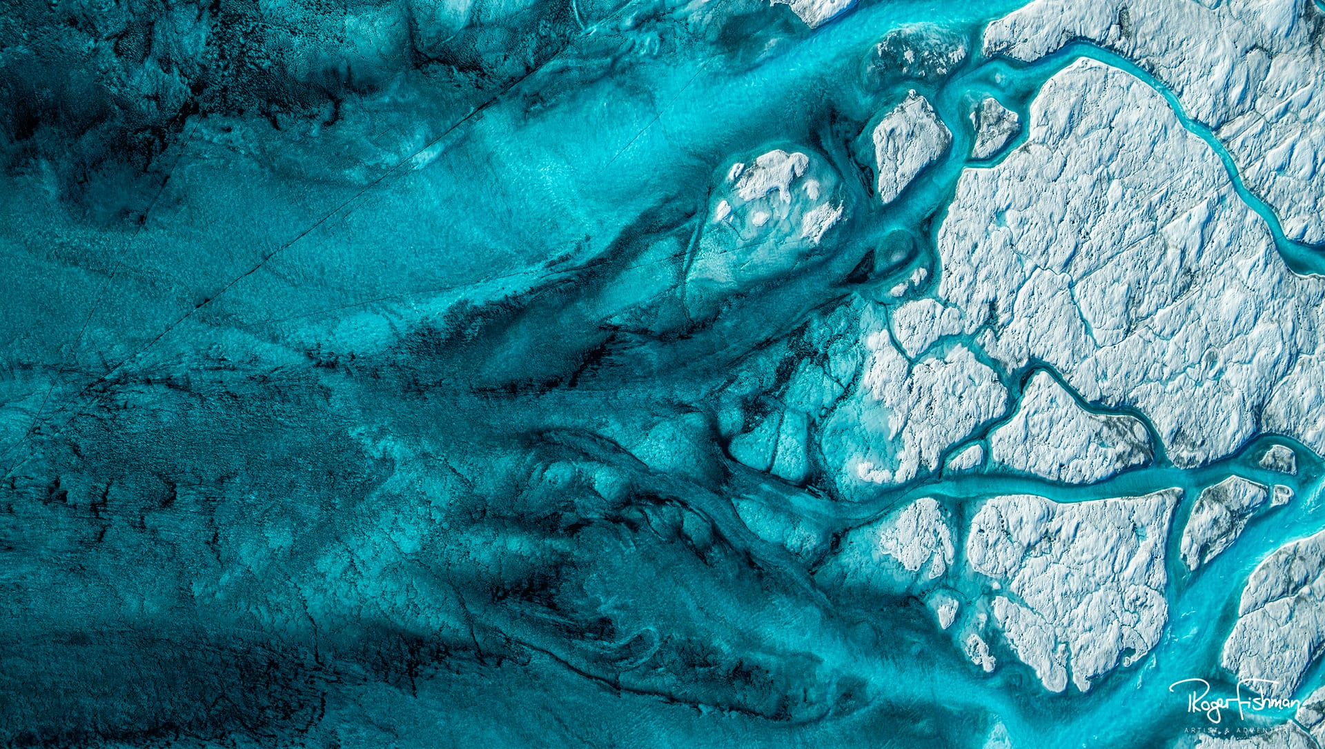 """Titled """"Aqua & Black #2,"""" this bird's eye view shows the vein-like patterns carved from annual meltwater on top of Greenland's glaciers, a once seasonal effect that has been exacerbated by climate change.  (© Roger Fishman)"""