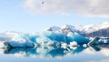 An iceberg reflects in the still waters of Jökulsárlón, Iceland (Photo courtesy of Jeremy Bishop via Unsplash)