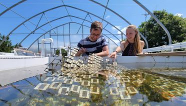 WHOI Postdoctoral scientist Taylor Nelson (Left) and PhD student Anna Walsh examining plastics exposed to sunlight in WHOI's outdoor experimental facility.  A new study finds that sunlight can break down marine plastic into tens of thousands of chemical compounds, at least ten-fold more complex than previously understood. Photo Credit: Woods Hole Oceanographic Institution