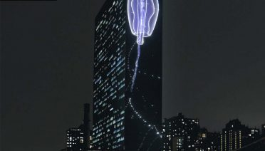 """A rendering of a video, """"Vertical Migration,"""" by Superflex, that is intended to draw attention to the siphonophore's deep sea carbon removal system. It will shine on the U.N. Secretariat building during Climate Week.Credit...Rendering via Superflex; Background by Eskinder Debebe/UN Photo"""