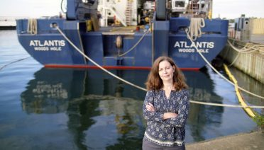 Alvin Certification Coordinator Lisa Smith standing in front of an updated HOV Alvin which is tucked on board the newly refurbished R/V Atlantis (Photo Ken Kostel ©WHOI).