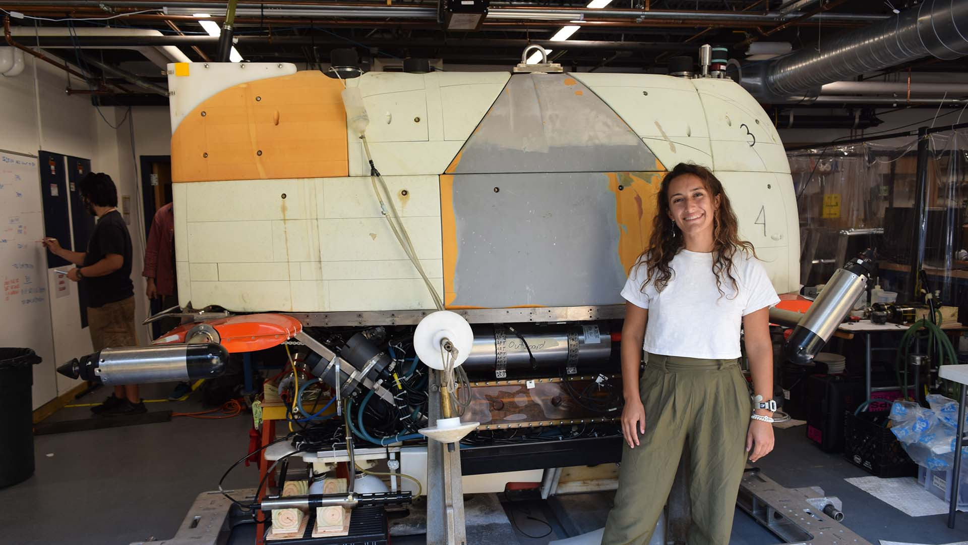 Renee Gruner-Mitchell with <em>Sentry</em> while the autonomous underwater vehicle was home for maintenance. In this picture the vehicle has its outer skin removed and syntactic foam showing. (Photo by Hannah Piecuch, © Woods Hole Oceanographic Institution)